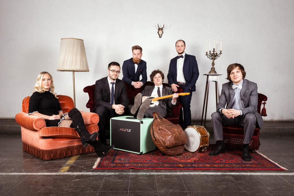 Fünf Bandmitglieder auf Sesseln, einer Couch und stehend