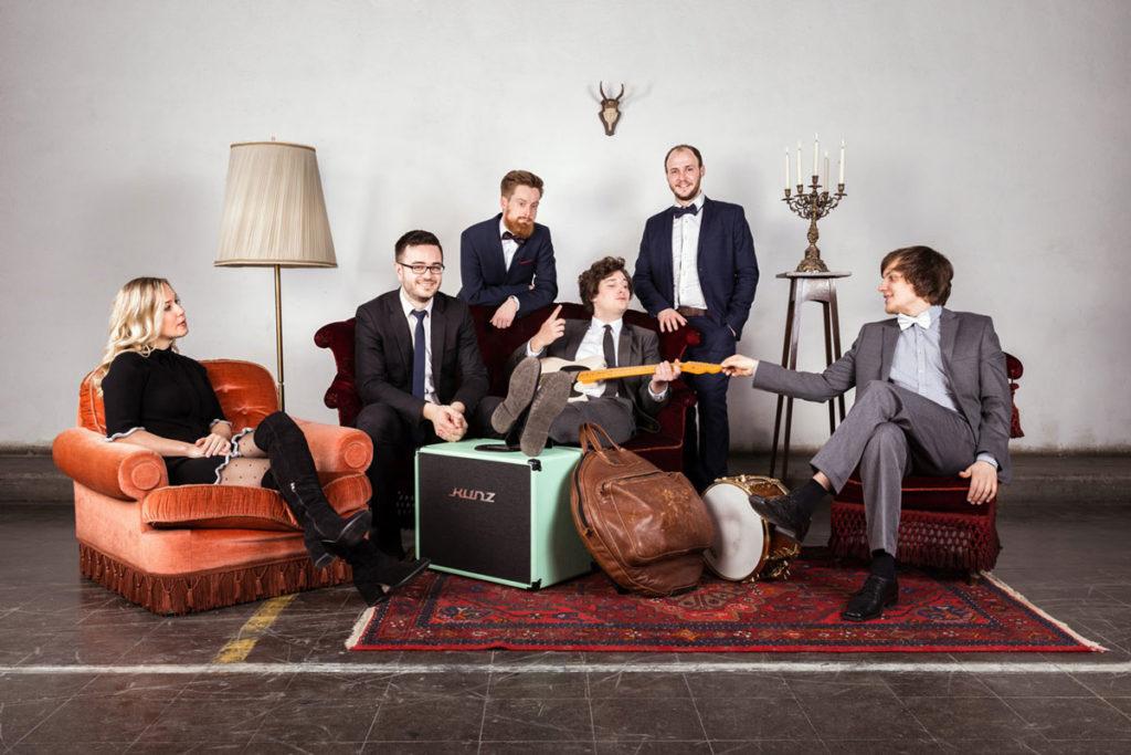 Fünf Bandmitglieder auf Sesseln und einer Couch