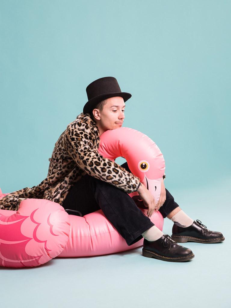 Junger Mann auf einem aufblasbaren Flamingo