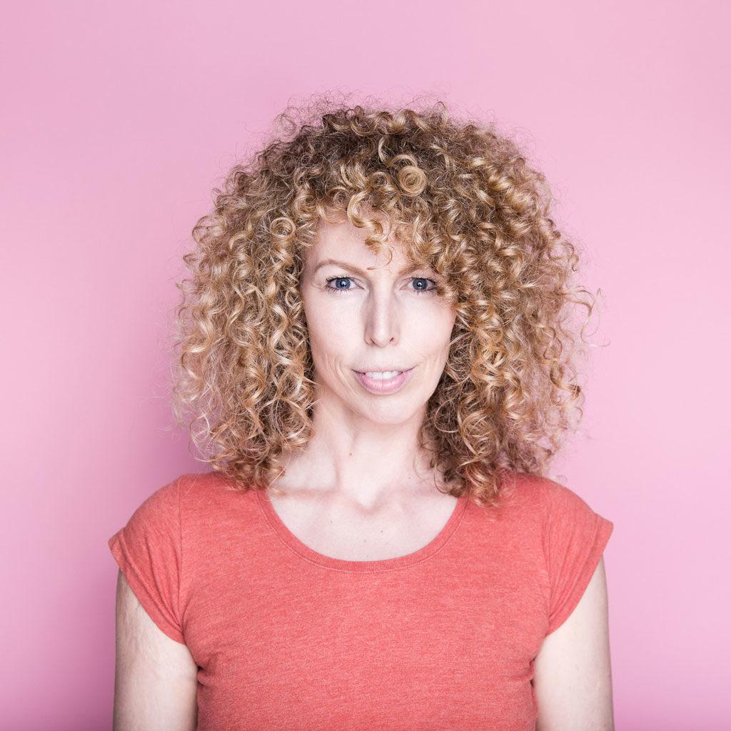 Frau mit Locken vor pinkem Hintergrund