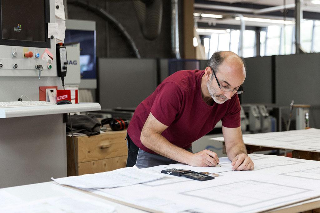 Ein Mann vor einem großen Bauplan