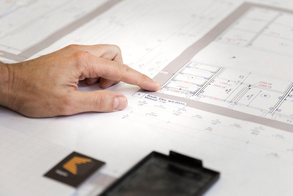 Finger zeigt auf einen Bauplan