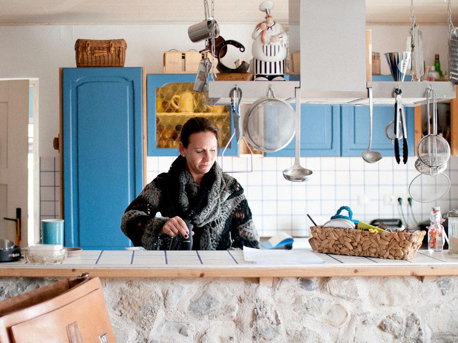 Frau hinter der Küchenzeile macht Kaffee