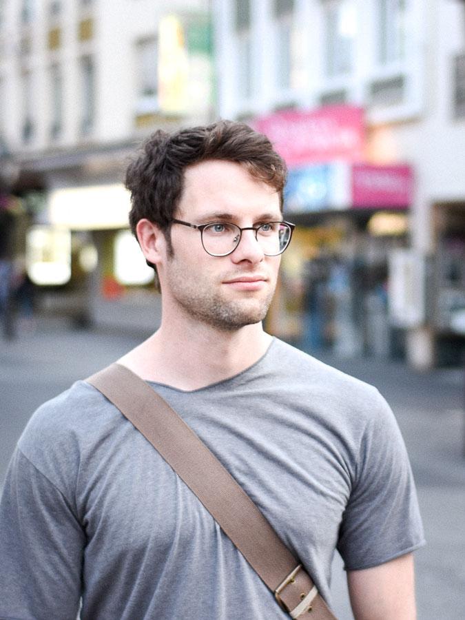 Junger Mann in einer Einkaufsstraße